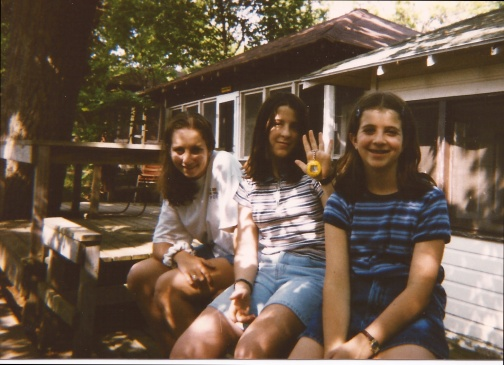 My sister, my friend Elizabeth, my super awesome Tamagotchi, and me in front of our cabin